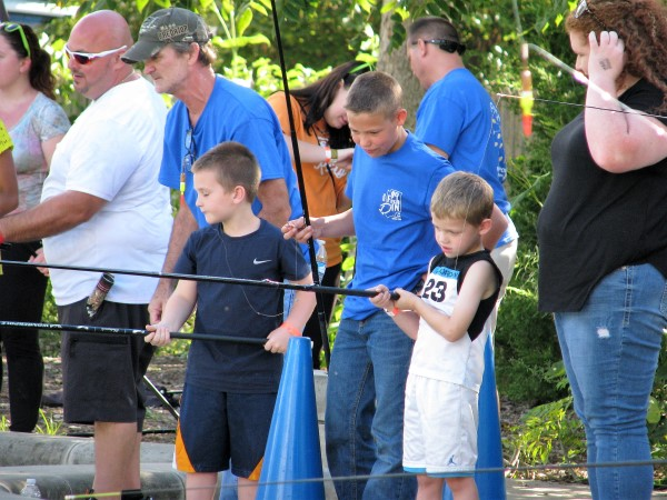 The volunteers, in blue shirts, gave personal attention to each child around the fishing pond.