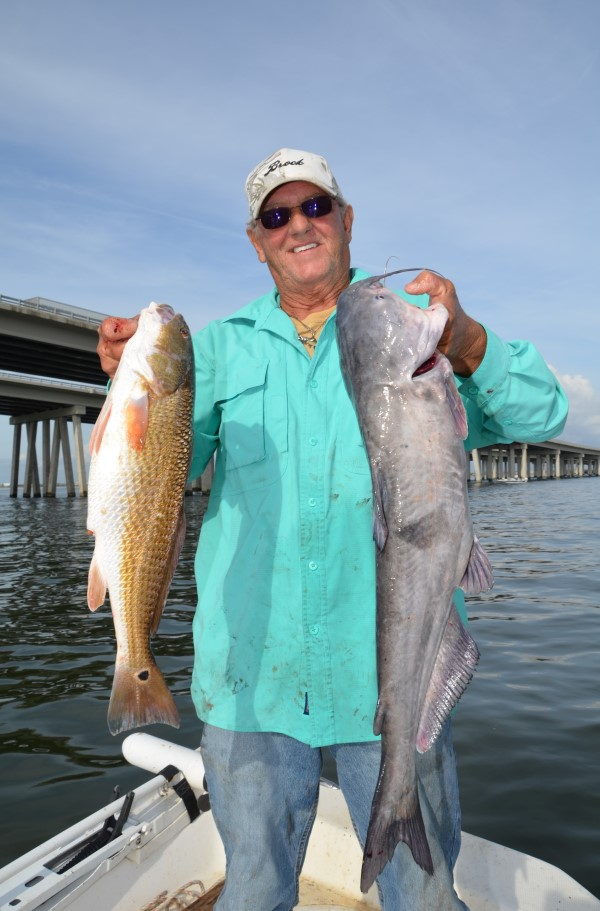 Capt. Kenny Kreeger, of Lake Pontchartrain Charters, shows off a redfish and a blue catfish he caught while fishing by the Interstate 10 Twin Spans crossing Lake Pontchartrain near Slidell, La.