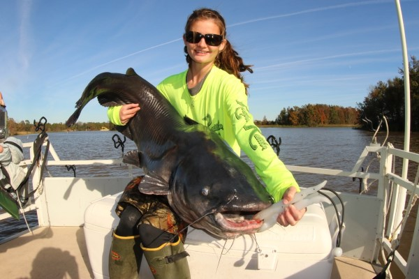Drifting puts catfish of all sizes in the boat, including this 76-pound trophy sitting in the lap of Julia Shillinglaw of South Carolina.